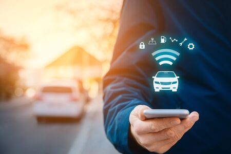 Intelligent car app on smart phone concept, intelligent vehicle and smart cars concept. Person with smart phone on street, car in background and wireless communication with car. Stock Photo