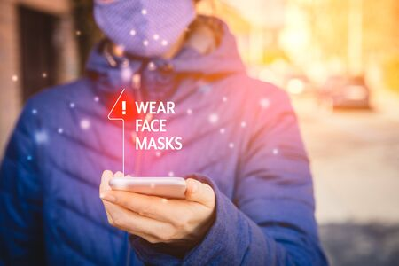 Wear face masks recommendation. Person with smart phone walk on street and look on wear masks notification on his mobile in pandemic times.