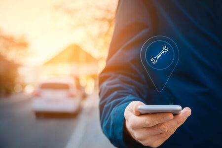 Search car service on smart phone. Smart car and new technologies in cars concept. Person with smart phone in hand walk on the sidewalk and search the nearest car service. Stock Photo