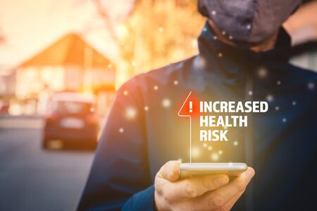 Increased health risk alert on smart phone concept. Person with mask and smart phone with notification about virus in epidemic times. Stock Photo