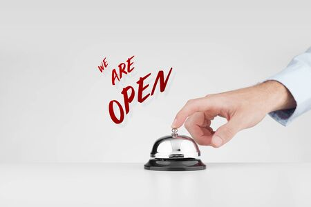 We are open advert concept. Marketing specialist beats alarm (press ring bell) to advertise shop, hotel or another service is open after quarantine close in covid era.