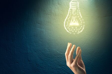 Turn on creativity, idea and intelligence concepts. Hand and graphics light bulb - symbols of idea, creative thinking, innovations and intelligence.