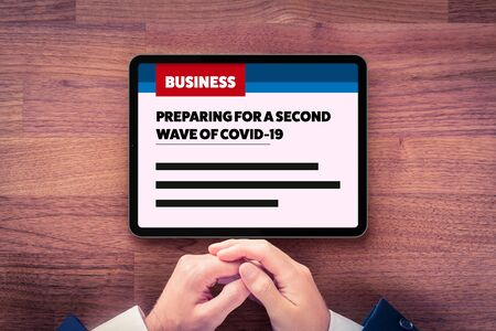Preparing for a second wave of covid-19 in business news. Businessman read how to prepare company for a second wave of coronavirus covid-19. Post-covid-19 era in business and investment concept.