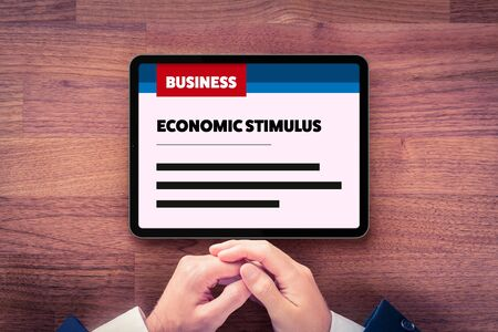 Manager read about economic stimulus after crisis. Government economic stimulus after covid-19 and another crisis times concept. Monetary and fiscal policy news. Zdjęcie Seryjne