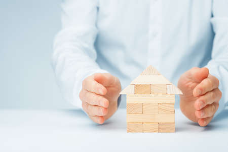 Property (family house) insurance protection concept. Insurance agent protect by hand model of the house made from wooden pieces.