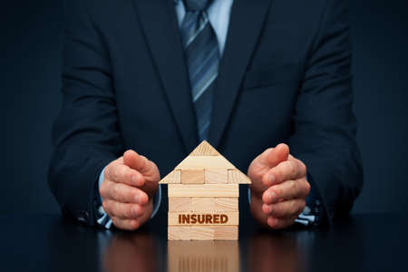 Property (family house) insurance protection concept. Insurance agent protect by hand model of the house with text insured, made from wooden pieces. Stock fotó