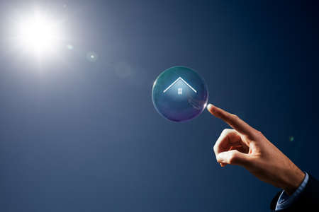 Catch chance of dream house concept. Hand with soap bubble (symbol of dream) with symbol of the house (property, real estate) inside.