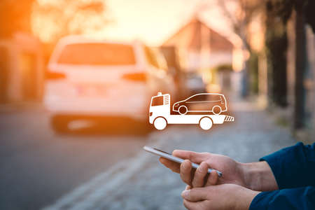 Search assistance service (wrecking towing breakdown service) on smart phone. Person with smart phone in hand sitting on the sidewalk and searching assistance service. Stock Photo