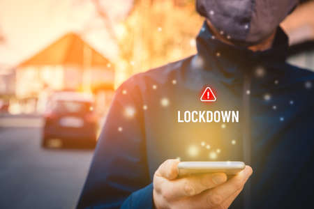 Lockdown notification concept on smart phone. Person with face mask as protection against covid-19 epidemic read alert on smartphone about lockdown.
