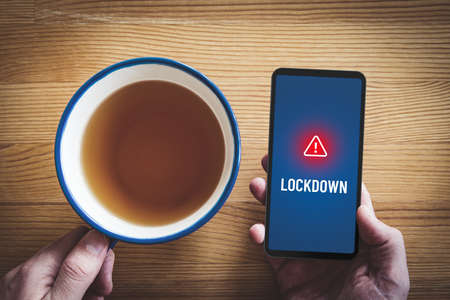 Lockdown notification concept on smart phone. Person read alert during breakfast on smartphone about lockdown. Zdjęcie Seryjne