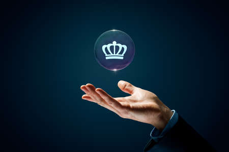 Dream about success concept and success in your hand. Hand with soap bubble (symbol of dream) with symbol of the success (crown) inside.