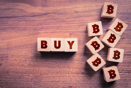 Buy bitcoin concept with wooden cubes. Wooden cubes with text buy and cubes with stylized symbol of bitcoin.