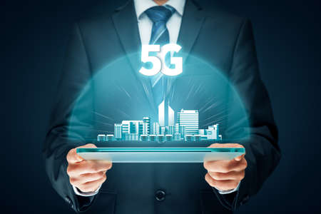 5G internet connection digital tablet concept. Person hold digital tablet with 5G broadband cellular network around city.