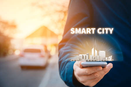 Smart city concept - communication technology (ICT) and Internet of things (IoT) technology integrated to manage city asset. Person with smart phone walk outside on street and symbol of a city. Imagens