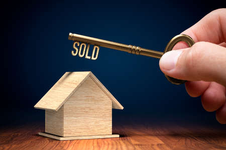 Sold real estate concept with key. Wooden model of house and key with text sold in hand. Key to successful selling of your property is in your hand.