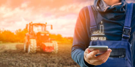 Intelligent agriculture concept with crop yield. Farmer or agrarian with smart phone looking on growing efficiency and crop yield, tractor in background. Smart agriculture and automation concept. Imagens