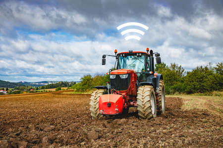 Autonomous tractor and intelligent agriculture concept. Autonomous tractor on plowed field communicate wireless with operator.