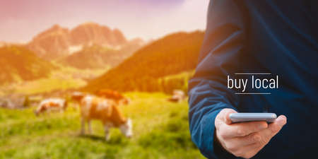 Buy local business model concept. Smart phone user buy agriculture products from local farmer. User with smart phone in hand and cows in beautiful landscape in background, text buy local.