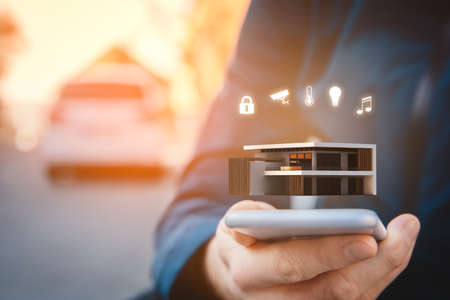 Smart home, intelligent house, and home automation app security concept. Smart phone user walking on street and set intelligent home settings on smart home app. Stock Photo