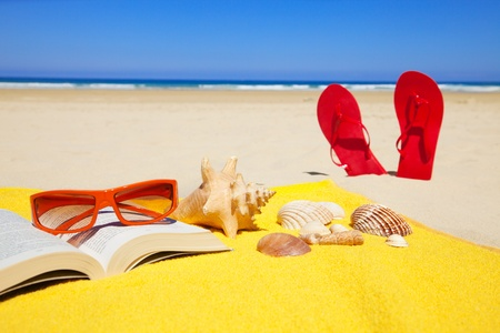 book, seashells, sunglasses on a towel and standing sandals in a deserted beach at a summer day with deep blue sky photo