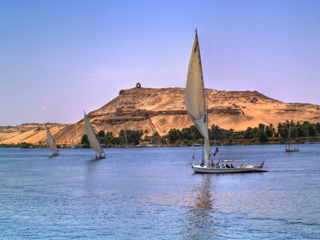 Images from Nile  Felukas sailing with Aswan ancient tombs as backgr Imagens