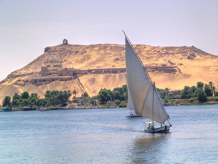 Images from Nile  Felukas sailing with Aswan ancient tombs as backgr