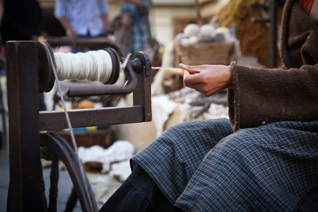 spinning wheel: woman using an old spinning wheel to turn wool into yarn