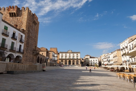 cityhall: 18 August 2011  Main square of Caceres, Spain in a sunny summer day  Panoramic view with the Bujaco Tower on the right and the Cityhall in the background  Visible some people walking or sit down in the terraces