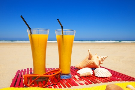 two orange juices, seashells and sunglasses on a deserted beach in a summer day with deep blue sky Stock Photo - 13170274