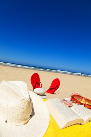 book, hat, seashells, sunglasses on a towel and standing sandals in a deserted beach at a summer day with deep blue sky