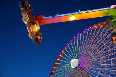 amusement park ride: Ferris wheel and carnival ride at night  Motion blur