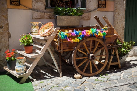 chiado: typical portuguese ceramics and small old wooden cart at the doors of a craft shop in Lisbon, Portugal