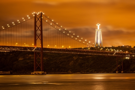 The 25 de Abril bridge over Tagus river and big Christ of Lisbon at night, Portugal