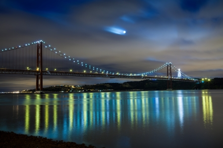 Panoramic of 25 de Abril bridge over Tagus river in Lisbon at night, Portugal