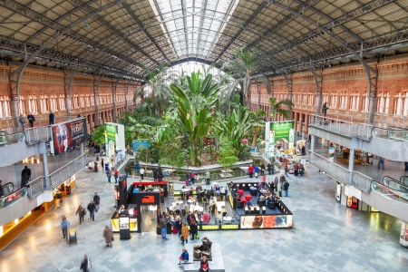 Madrid, Spain - December 14, 2012: Atocha station. Christmas market, shops, cafes and a botanical garden forming the entrance to the new station
