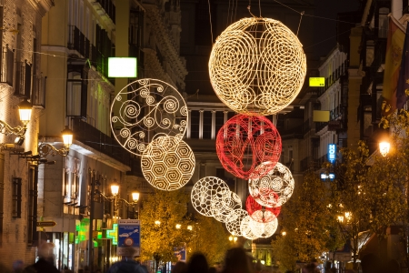 Arenal street of Madrid illuminated for christmas, near the Puerta del Sol , the Opera building as background