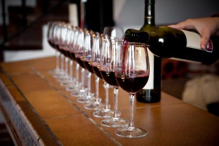 Vrouw hand met fles wijn gieten van een rij van glazen voor het proeven Stockfoto