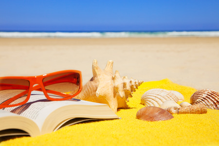 beach towel: book, seashells, sunglasses on a towel in a deserted beach at a summer day with deep blue sky