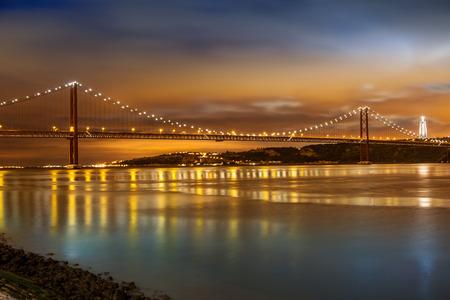 夜、ポルトガル リスボンのテージョ川に架かる 25 de Abril 橋パノラマ