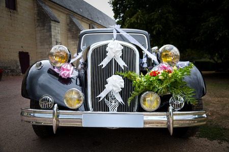 Vintage wedding car decorated with flowers and ribbons. Clipping path included