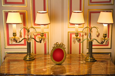 scenary: Marble dresser with classic lamps and old empty portrait