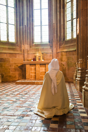 Sister praying into the Abbey of Mont St. Michel, France