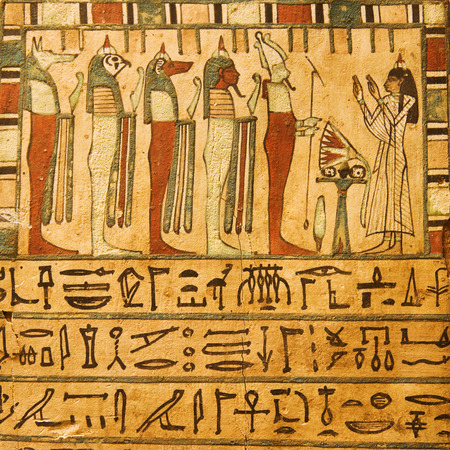 Ancient Egyptian gods and hieroglyphics painted on stone