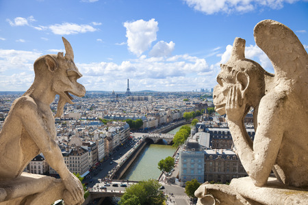 paris vintage: Notre Dame of Paris: Famous Chimeras overlooking the skyline of Paris at a summer day