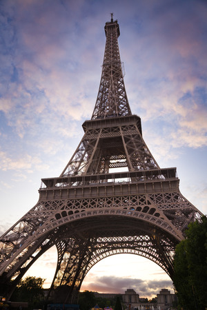 Eiffel Tower: Wide low angle of Eiffel Tower against a nice cloudy sky at sunset Stock Photo
