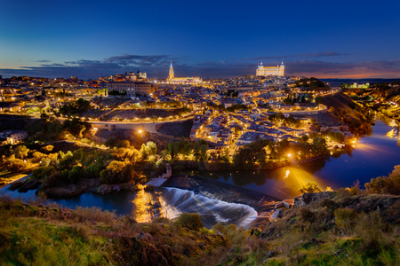 to dominate: Great panoramic of historic city of Toledo at night, Spain. The Alcazar on the right and Cathedral on the left dominate the skyline