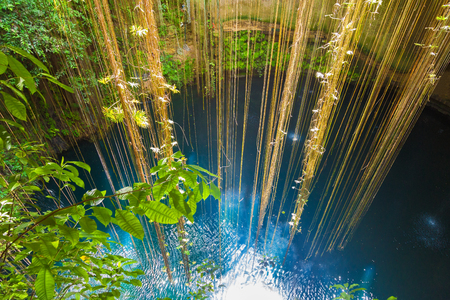 misterious: Top view of Ik-Kil Cenote, near Chichen Itza, Mexico. Lovely cenote with transparent waters and hanging roots Stock Photo