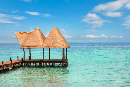 riviera maya: wooden pier and fishing boats on a Caribbean beach with turquoise waters