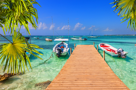 beach panorama: wooden pier and fishing boats on a Caribbean beach with transparent waters