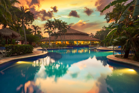 Luxury swiming pool in a tropical resort at sunset